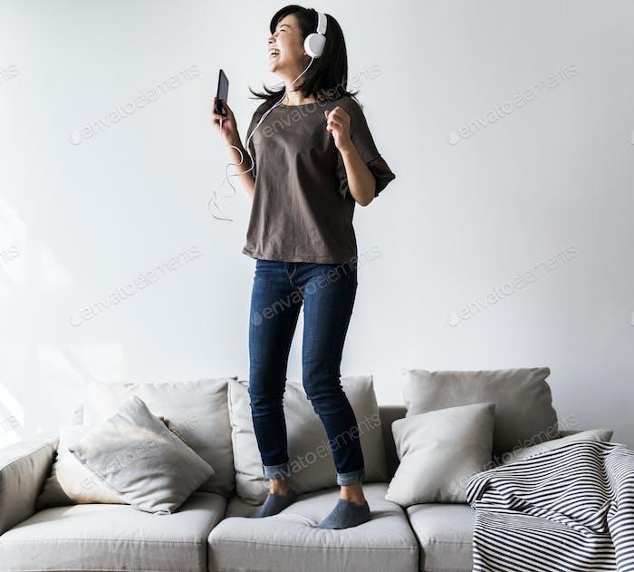 Asian woman enjoying music at home