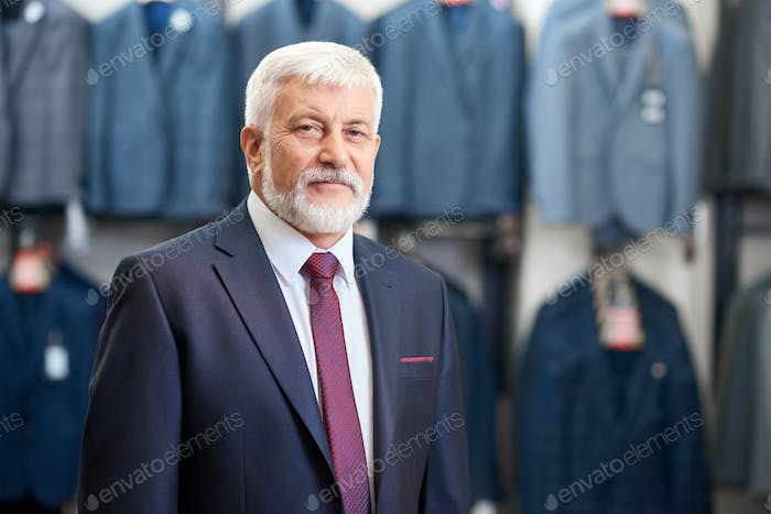Senior man standing in store clothes for men