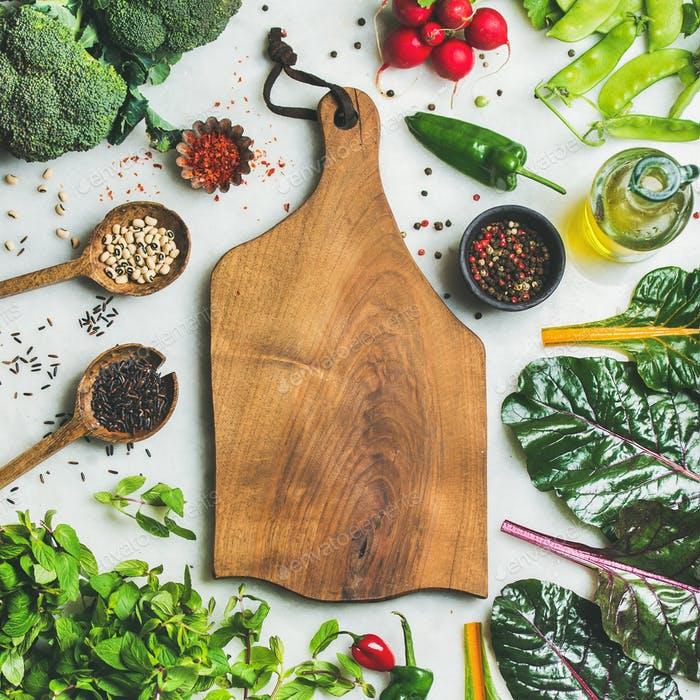 Fresh greens, vegetables and grains with wooden board in center