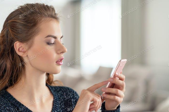 Attraktive junge Frau Blick auf ihr Smartphone zu Hause