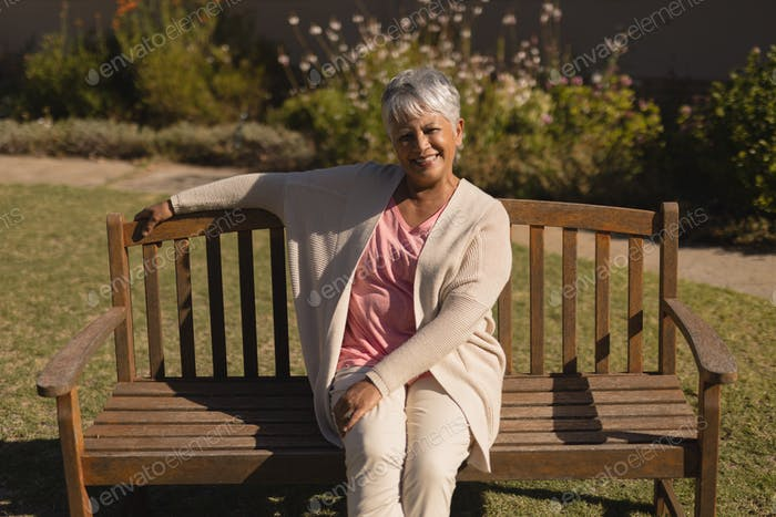Front view of active happy senior woman sitting on a bench in the park on sunny day
