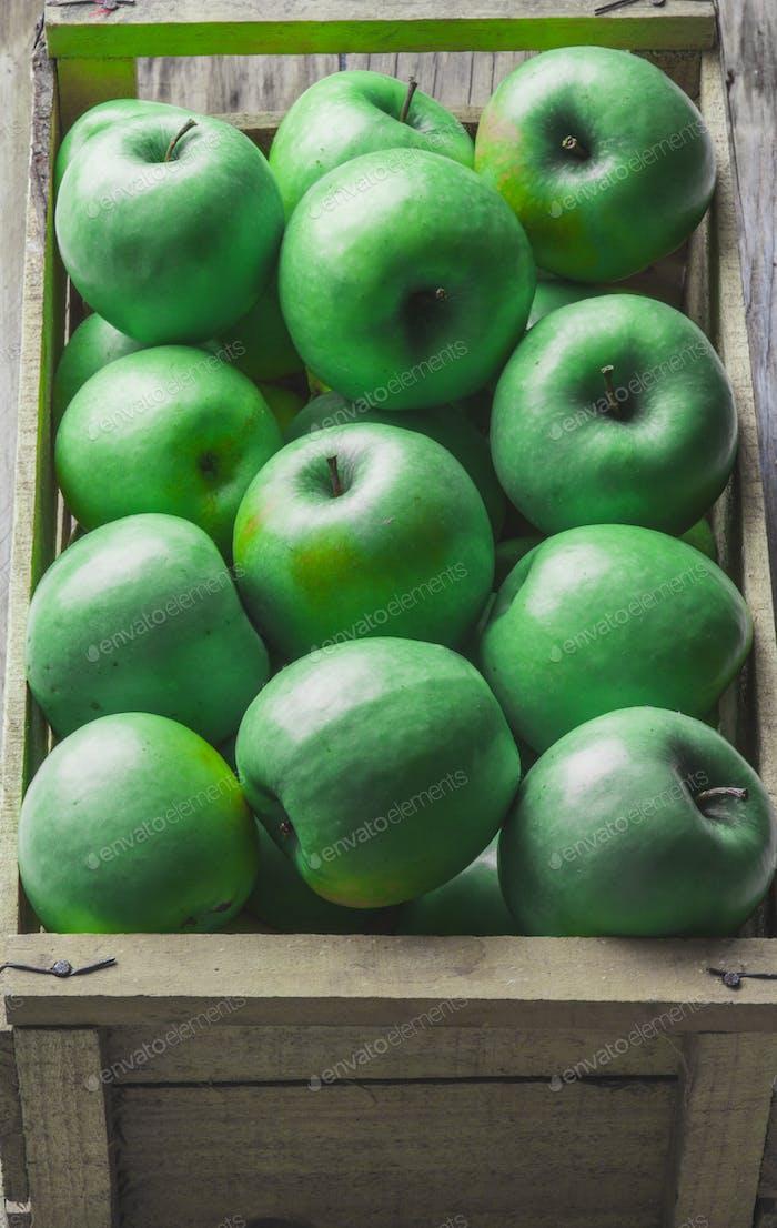 Grüne Äpfel in Holzkiste. Erntekonzept