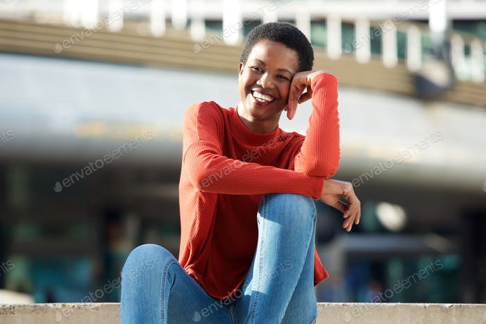 happy young black woman sitting sitting outside in city