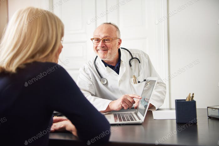 Cheerful adult medical worker showing laptop to patient