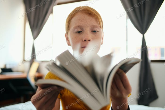 Young Redhead Girl Studying And Holding Book