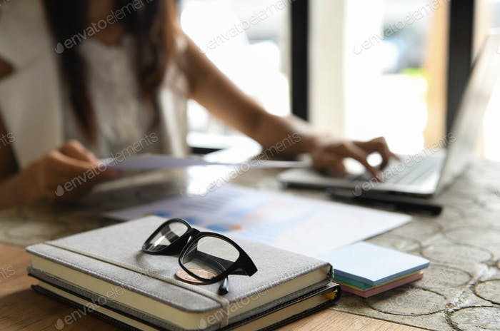 Glasses placed on notebooks, background blurred people are sitting using laptop.