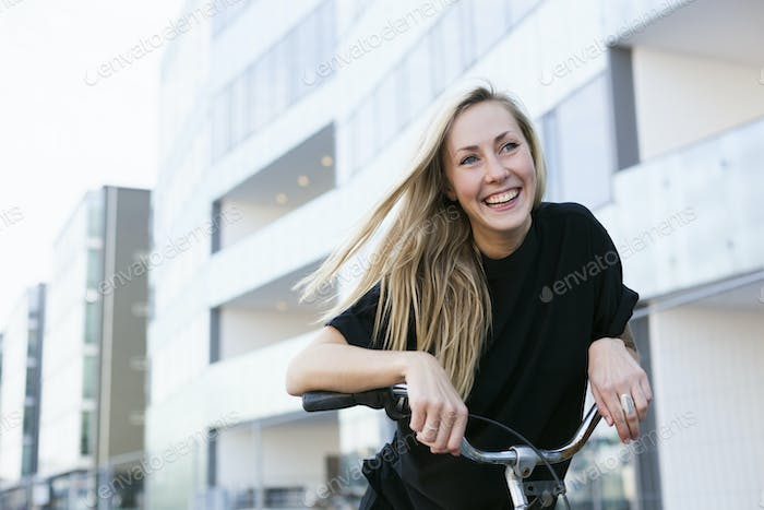 Cheerful female college student leaning on bicycle against building