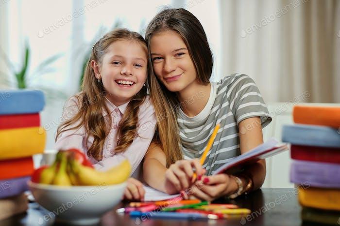 Freundinnen lernen am Tisch mit vielen Büchern.
