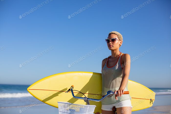 Front view of African american woman with surfboard sitting on bicycle at beach in the sunshine