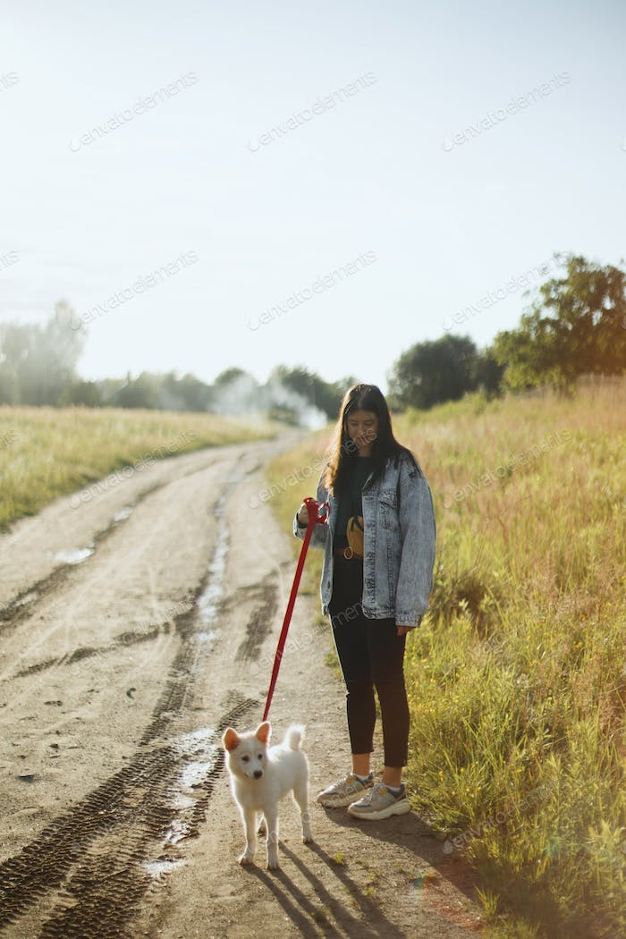 Stylish hipster girl walking with cute white puppy in summer park