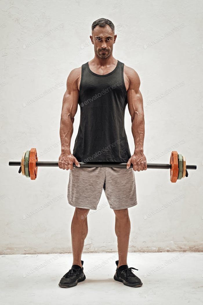 Strong and sportive fitness trainer holding a barbell isolated in a studio