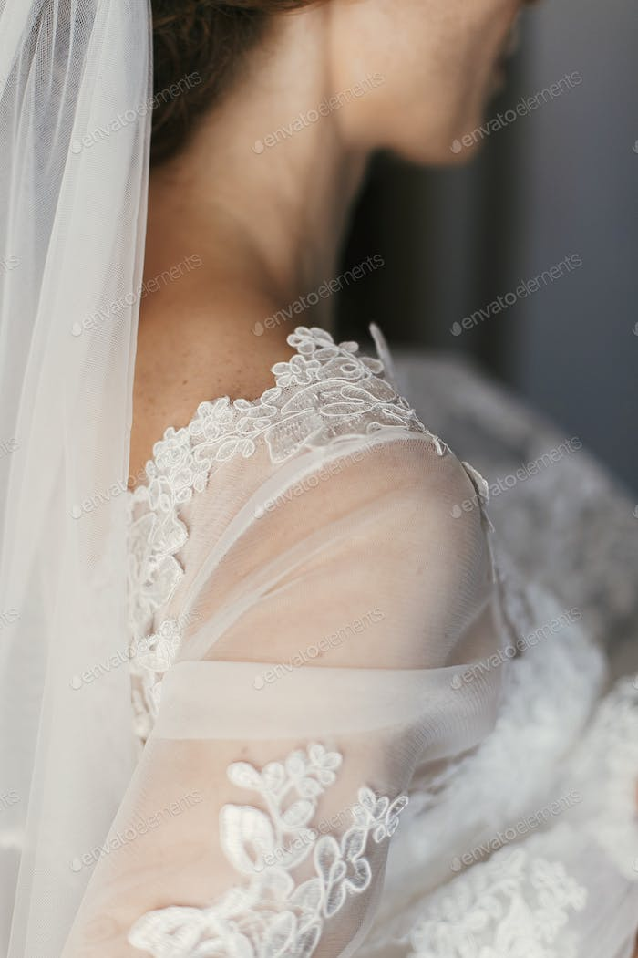 Beautiful bride shoulder in luxury silk wedding dress with lace floral elements