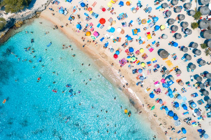 Aerial view of sandy beach with colorful umbrellas