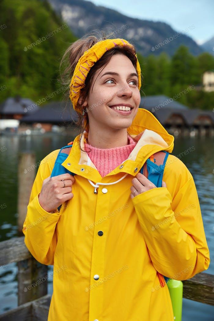 Fröhliche europäische Touristin reist in den Bergen, posiert in der Nähe des Sees, genießt sonnigen warmen Tag, trägt