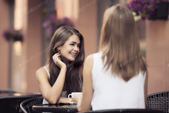 Smiling Young Women Drinking Coffee And Talking Outdoor