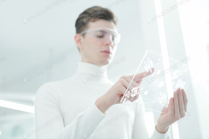 Hands of contemporary app developer pointing at display of transparent tablet