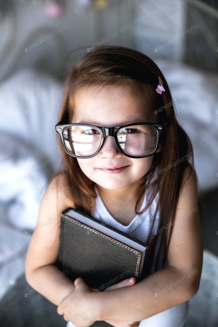 Thumbnail for Preschooler girl with books and glasses. teaching, student, education