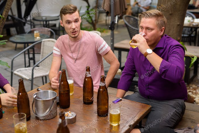 Group of men outdoors sitting and talking while drinking beer