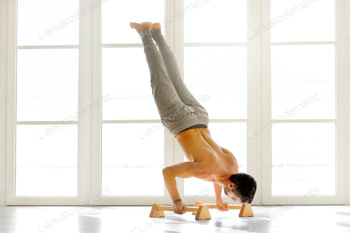 Man doing handstand push ups on bars