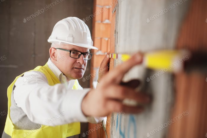 Man Working As Architect Measuring Wall In Construction Site