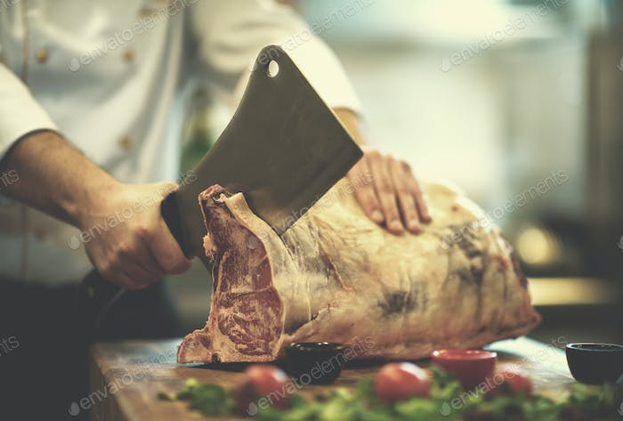 chef cutting big piece of beef