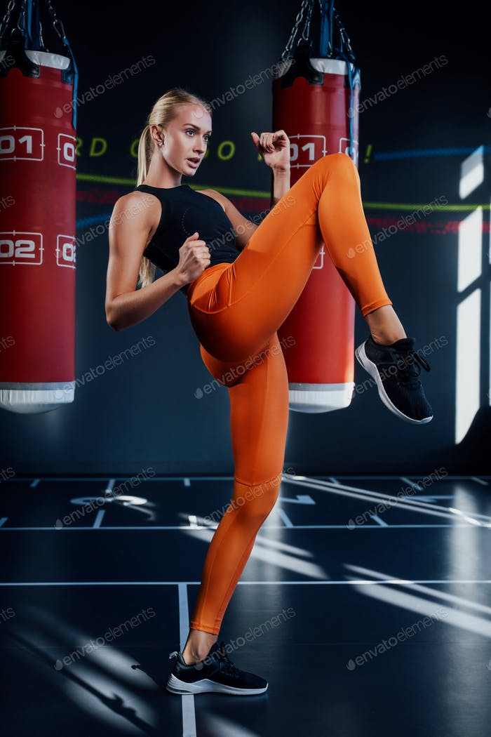 Blond sportswoman punching with foot in sport club