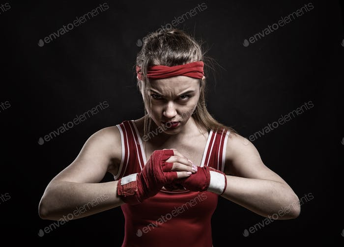 Female kickboxer training in gym, boxing workout