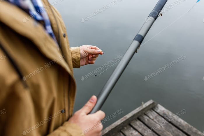 partial view of fisherman with fishing rod and hook on wooden pier at lake