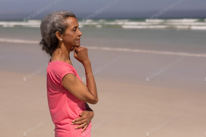 Side view of thoughtful senior woman with hand on chin standing on beach in the sunshine