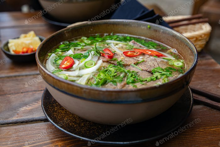 Close-up of fresh Pho soup in bowl served on table