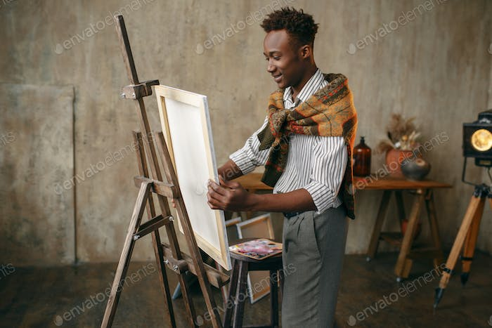 Happy painter prepares easel with canvas