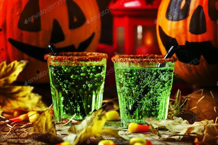 Halloween-Komposition mit festlichem grünen Getränk und lächelndem Trinken Kürbis