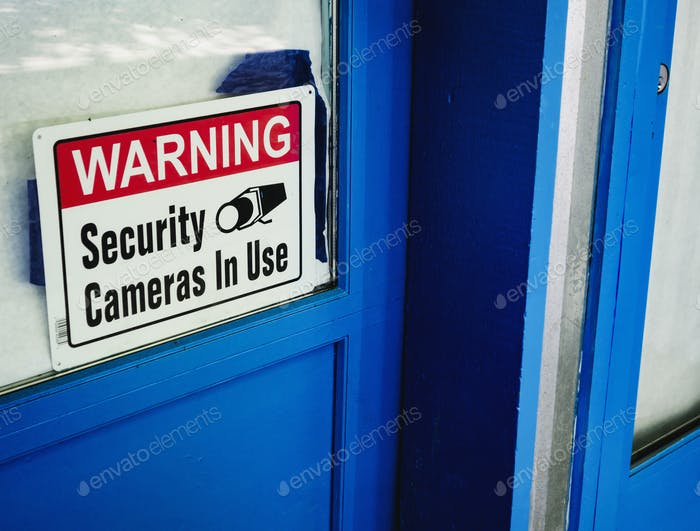 Security camera sign in a shop window.