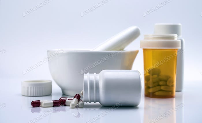 Capsules red and white out of a bottle next to mortar pharmacist, conceptual image