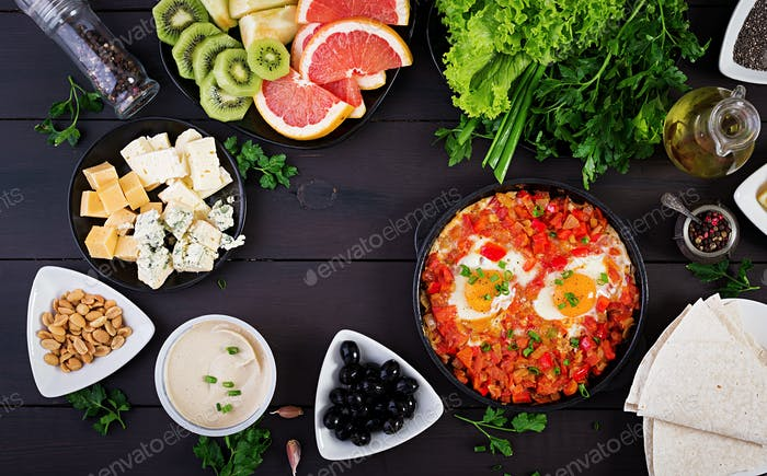 Turkish Breakfast -  shakshuka, olives, cheese and fruit. Rich brunch. Top view