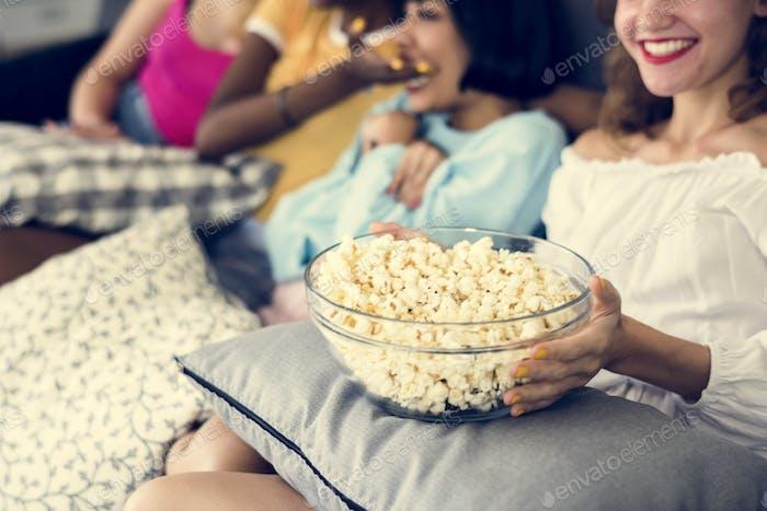 Diverse women eating popcorn together