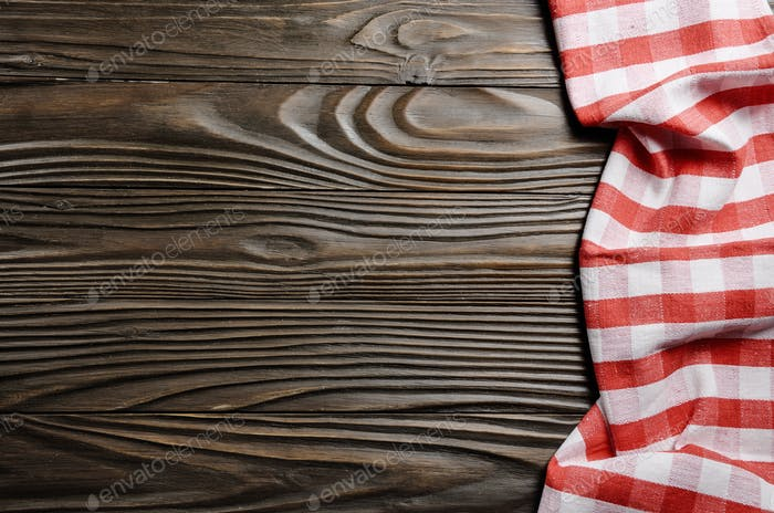 Red checkered napkin on brown wooden kitchen table with copy-space. Top view