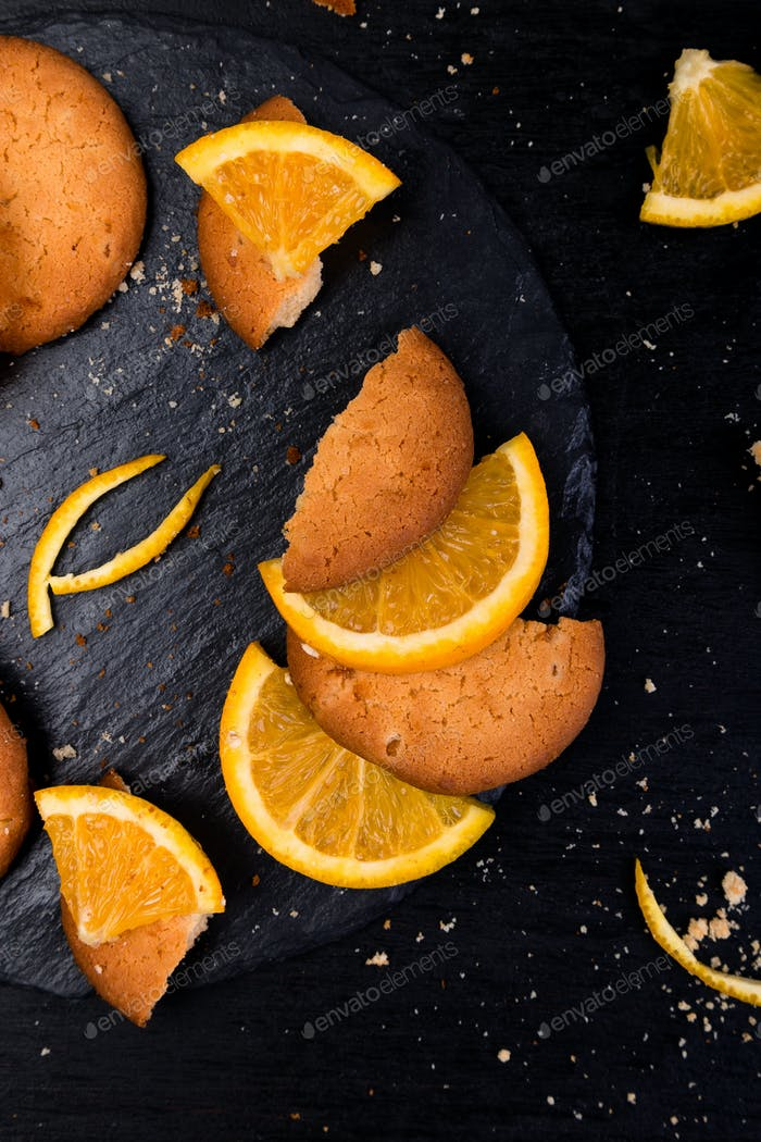 Cookies and orange citrus fruit on slate plate on black background. Flat lay