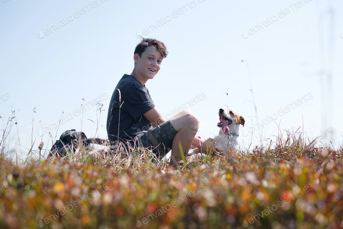 Teenager on autumn lawn with small white dog