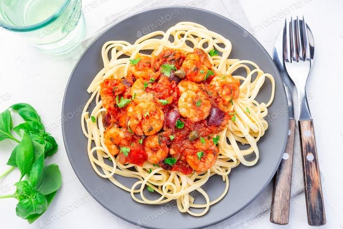 Linguine Puttanesca Pasta mit Garnelen in würziger Tomaten-Basilikum-Sauce horizontal, Draufsicht