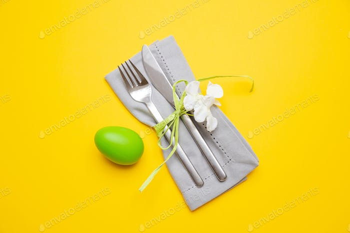Easter egg, green color painted, cutlery and grey napkin, yellow background, top view
