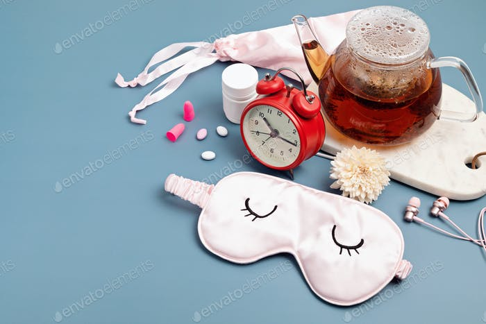 Alarm clock, sleeping mask, tea pot on blue background. Quality of sleep, good night, insomnia