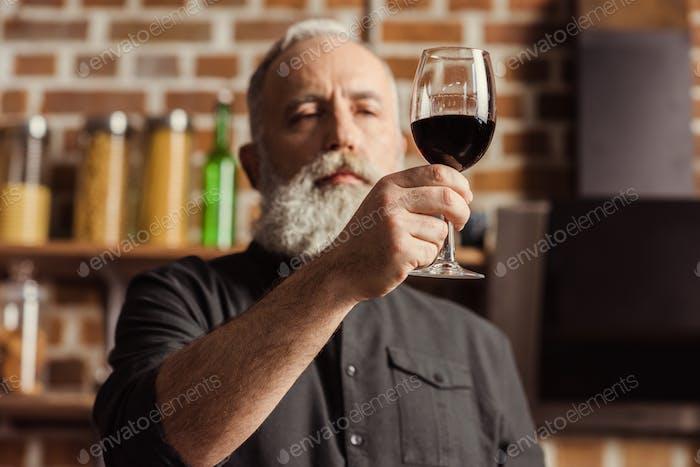 Bärtiger Seniorenmann Blick auf Weinglas mit Rotwein