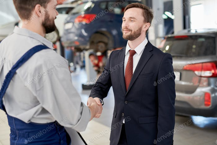 Businessman Shaking Hands with Mechanic