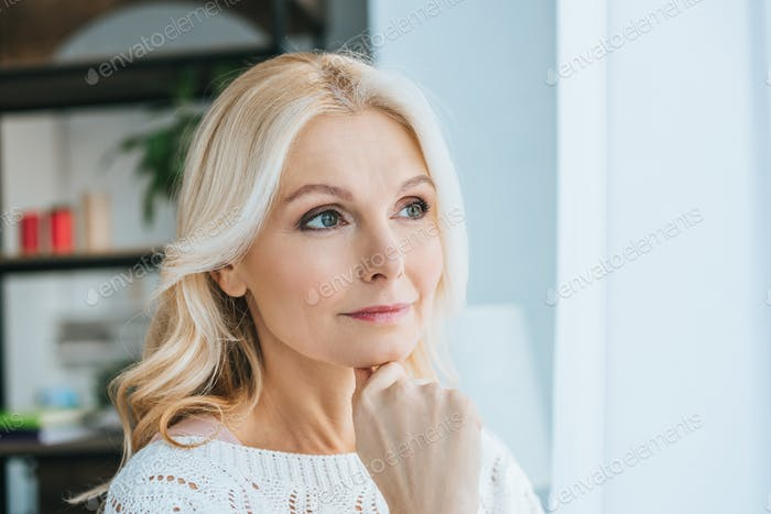 pensive woman standing and thinking at home