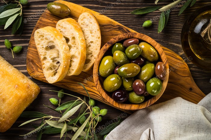 Olives, olive oil and ciabatta on wooden table