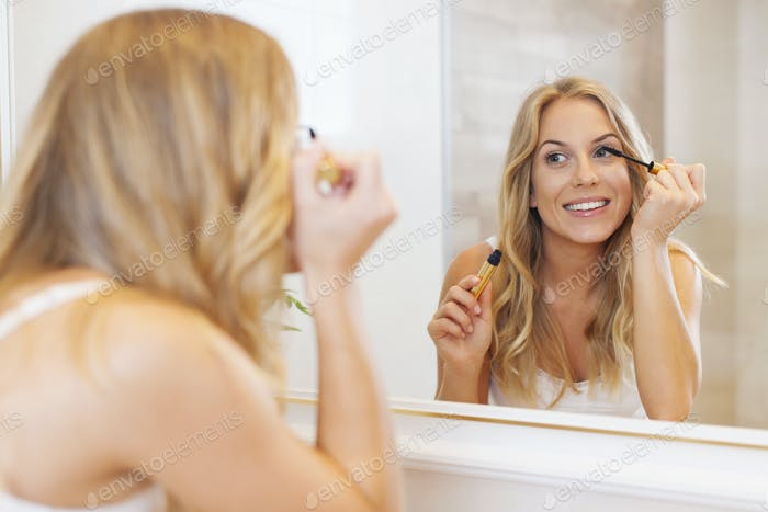 Lovely woman applying mascara in front of mirror