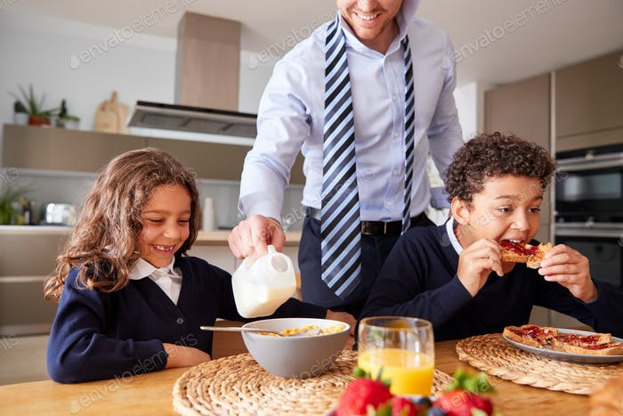 Businessman Father In Kitchen Helping Children With Breakfast Before Going To School