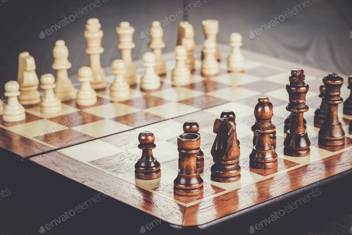 Schachbrett mit Figuren auf Holztisch