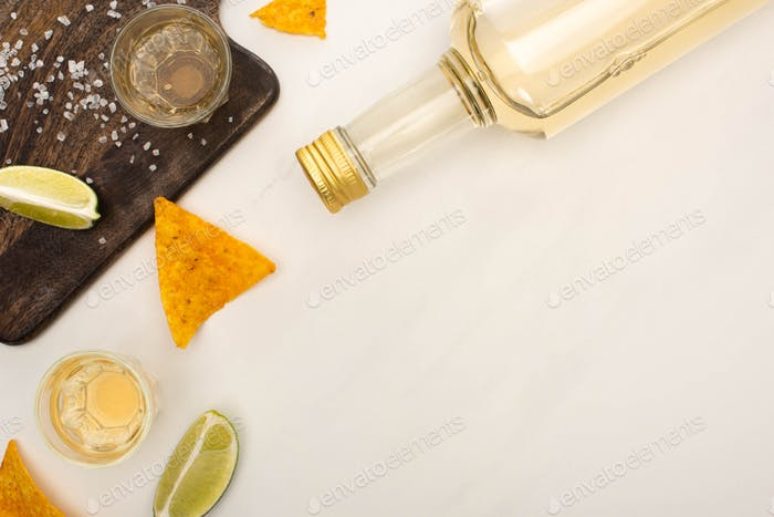 top view of golden tequila with lime, salt and nachos